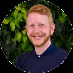 Andreas Janßen, vor dunkelgrünem Hintergrund, rötliche kurze Haare, rötlicher Bart, lächelnd, dunkelblaues Oberteil