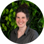 Anna Britz vor dunkelgrünem Pflanzenhintergrund, dunkelgraues Hemd, dunkle Haare zu Dutt, kleine goldene Ohrringe, lächelnd