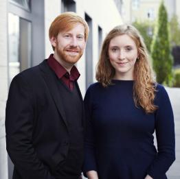 Tim Janßen mit rötlichen kurzen Haaren und Bart, schwarzes Sakko, und Nora Sophie Griefahn daneben, rötliche Haare lang, blaues Kleid, beide lächeln