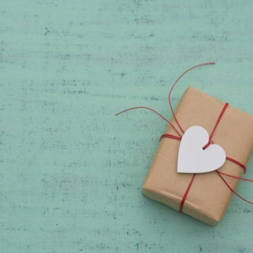 Geschenk mit Herzanhänger vor türkisem Hintergrund