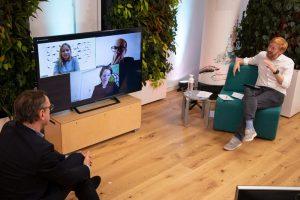 Zwei Männer vor Bildschirm mit Gesichtern von Menschen in Diskussion; Blog von Cradle to Cradle NGO