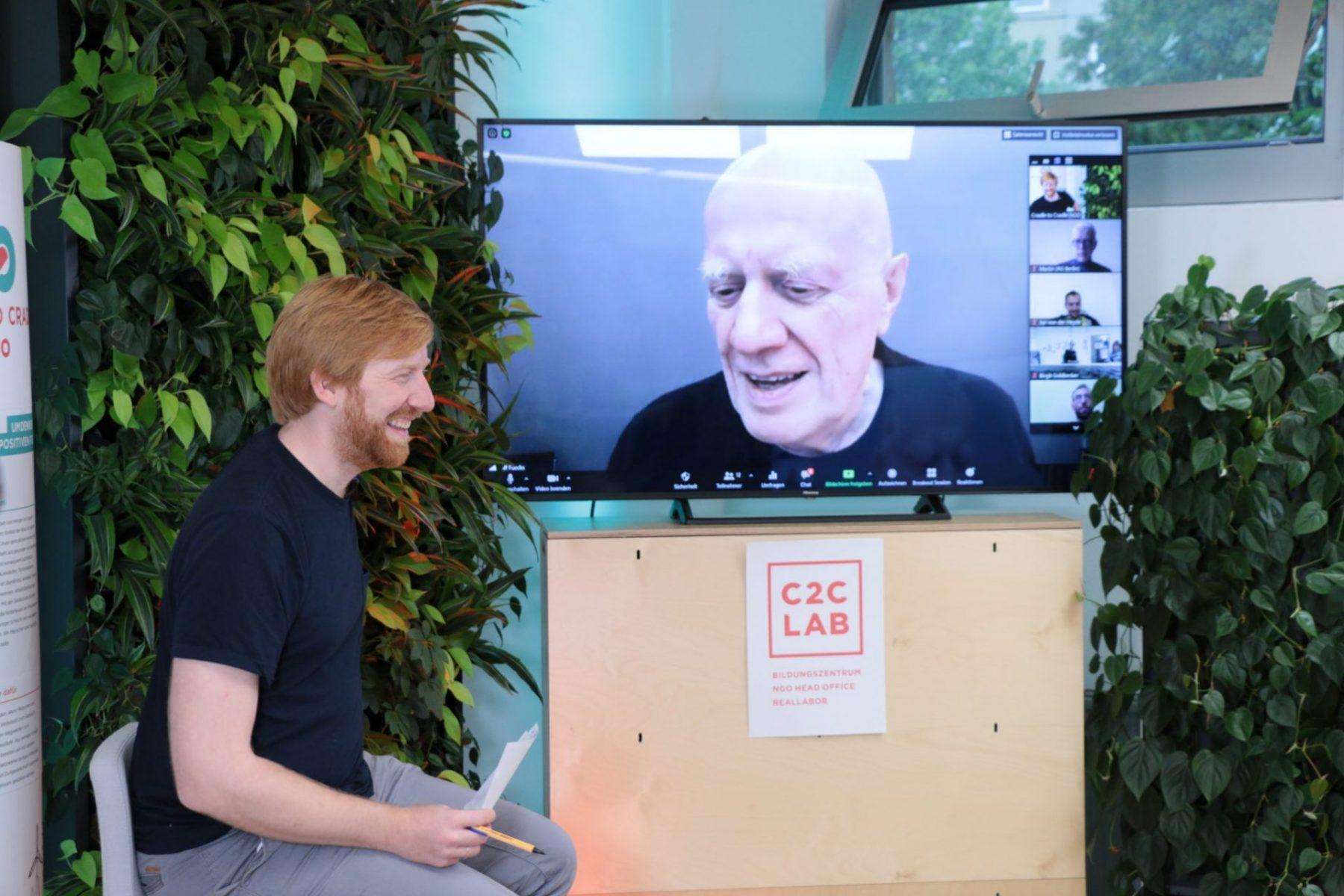 Tim Janßen sitzt auf Stuhl vor Bildschirm mit Gesicht von Ralf Fücks; Blog von Cradle to Cradle NGO