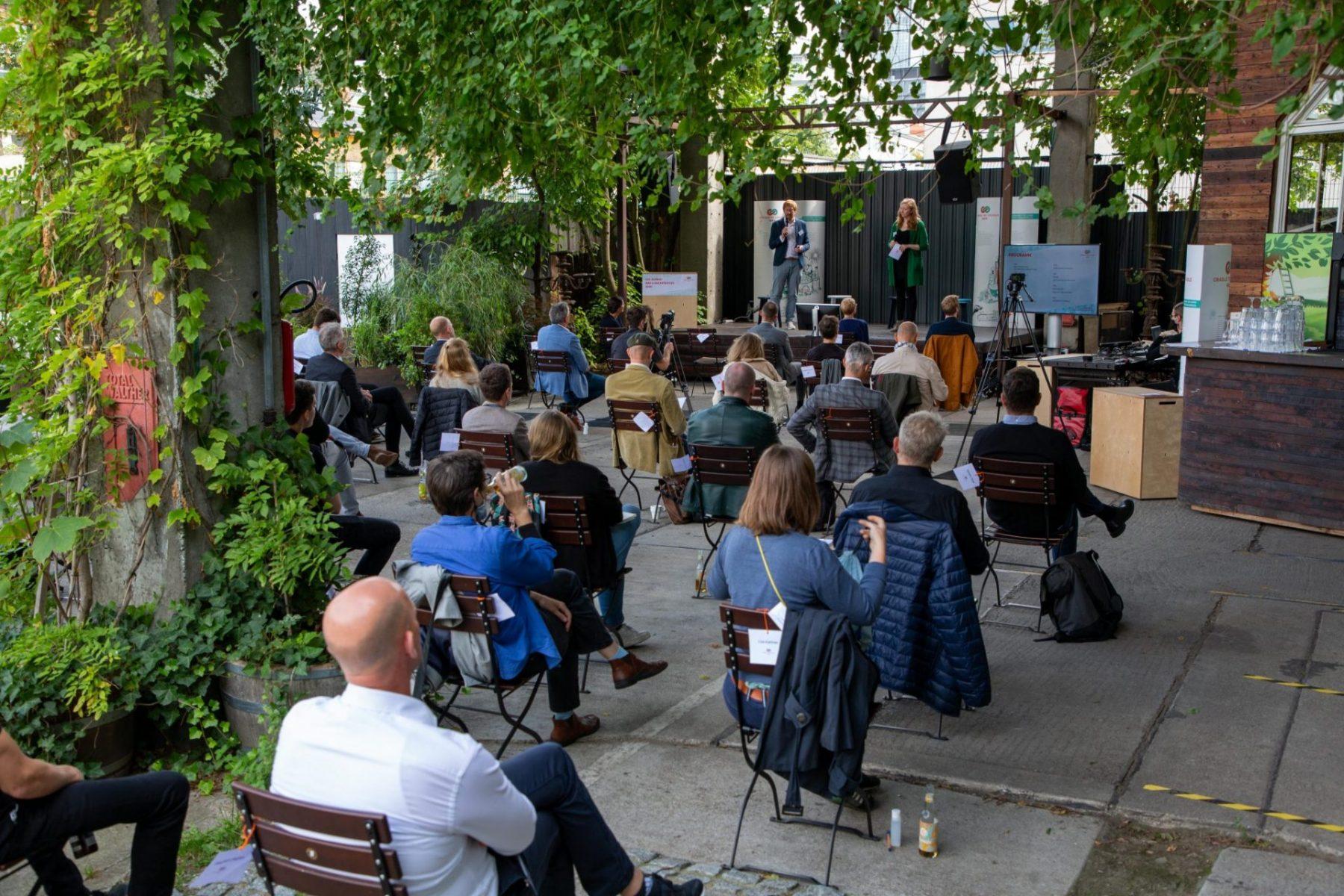 Menschen sitzen draußen vor Bühne auf Stühlen; Blog von Cradle to Cradle NGO