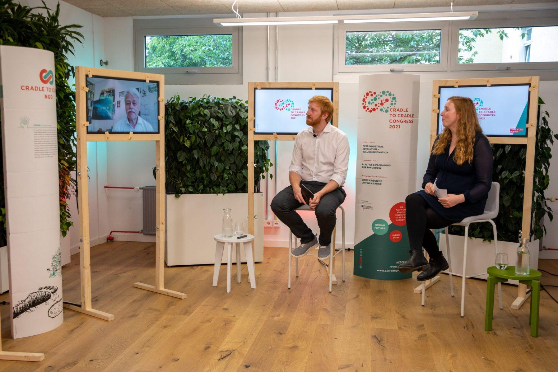 Nora und Tim vor Kameras neben Bildschirmen in Holzrahmen, sitzend