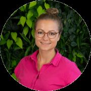 Jana Mätz vor dunkelgrünem Pflanzenhintergrund, blonde Haare zu Dutt gemacht, pinkes Poloshirt, mittelbraune Brille, lächelnd