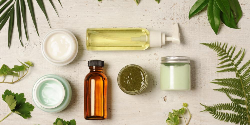Kosmetikverpackungen und Blätter vor hellem Hintergrund, Blog von Cradle to Cradle NGO