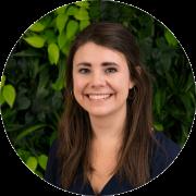 Lorena Zangl vor dunkelgrüem Hintergrund, lächelnd, dunkelbraune mittellange Haare