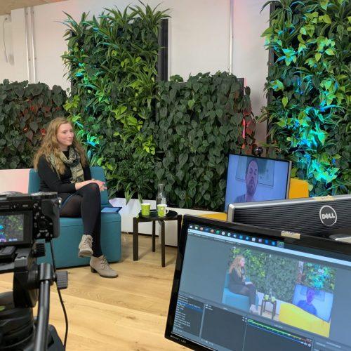 Nora Griefahn im C2C LAB vor Kameras sitzend vor begrünten Wänden